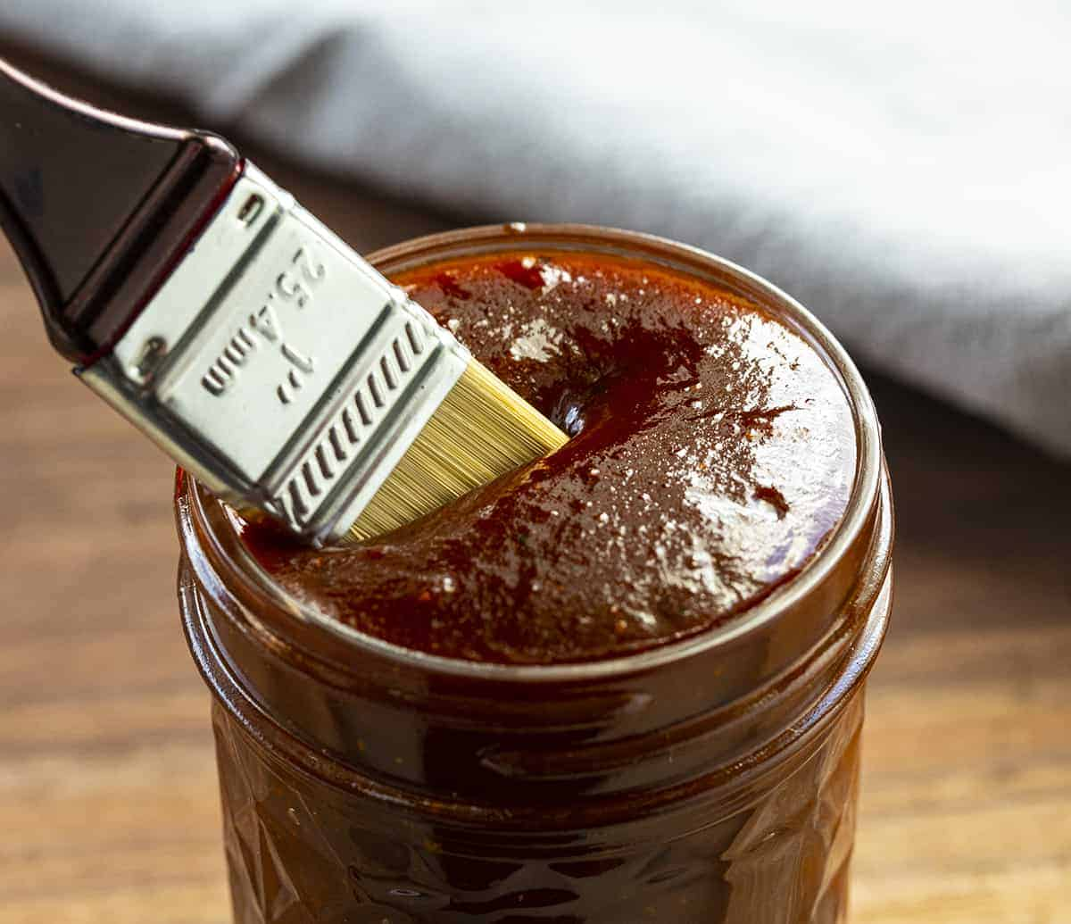 Dipping Brush into BBQ Sauce in a Jar