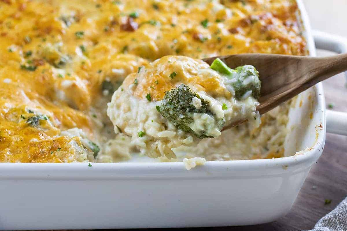 Broccoli Chicken Rice Casserole Pan with Wooden Spoon Holding Some