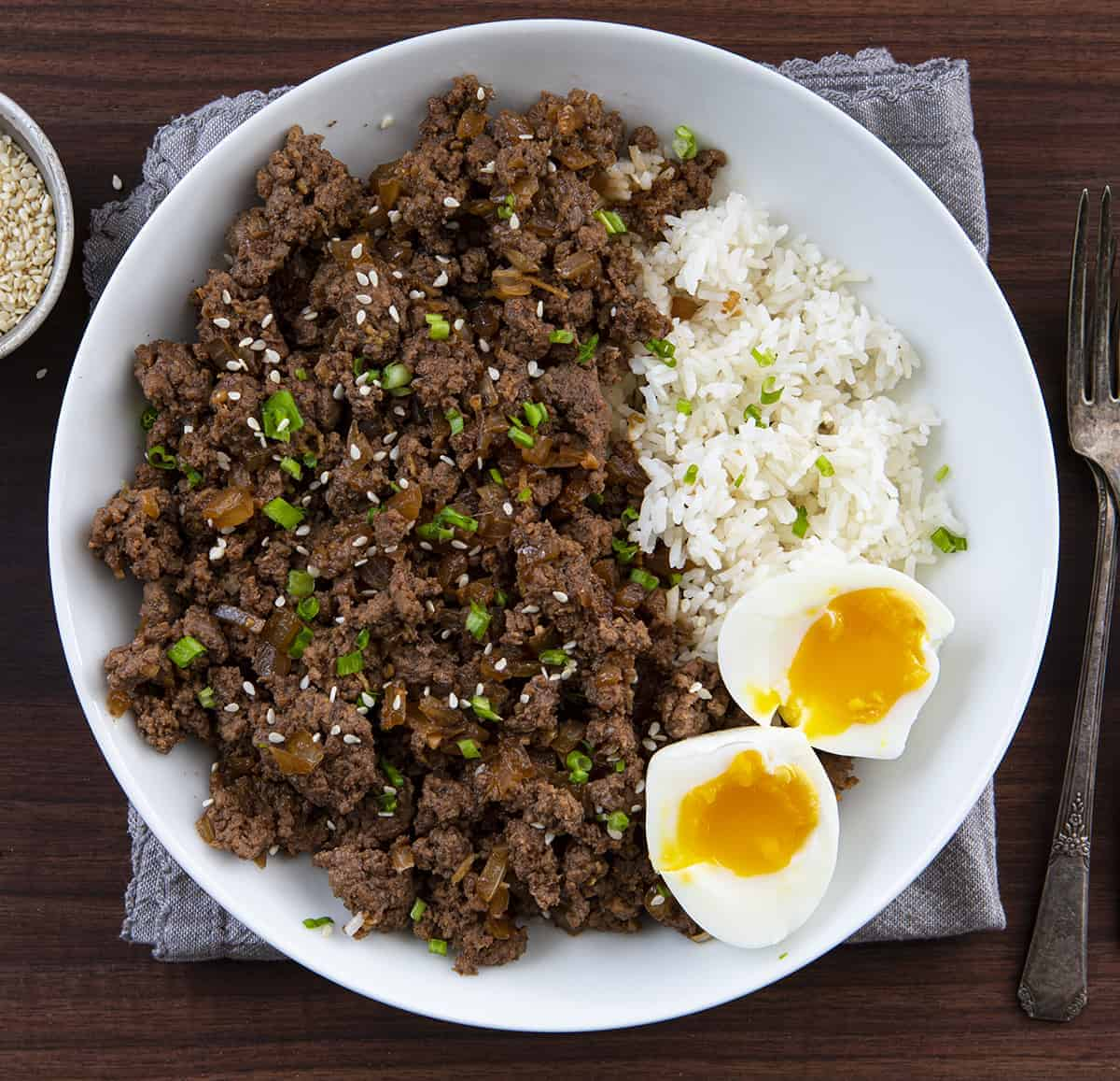 Overhead Image of Beef Bulgogi in a White Bowl with Rice and Eggs