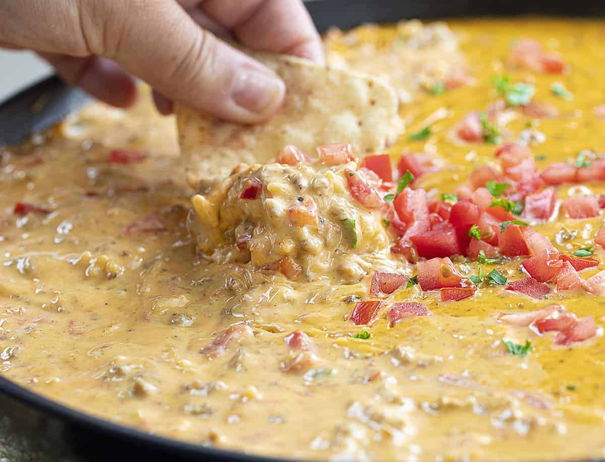 Hand Dipping Chip in Hamburger Rice Dip Recipe