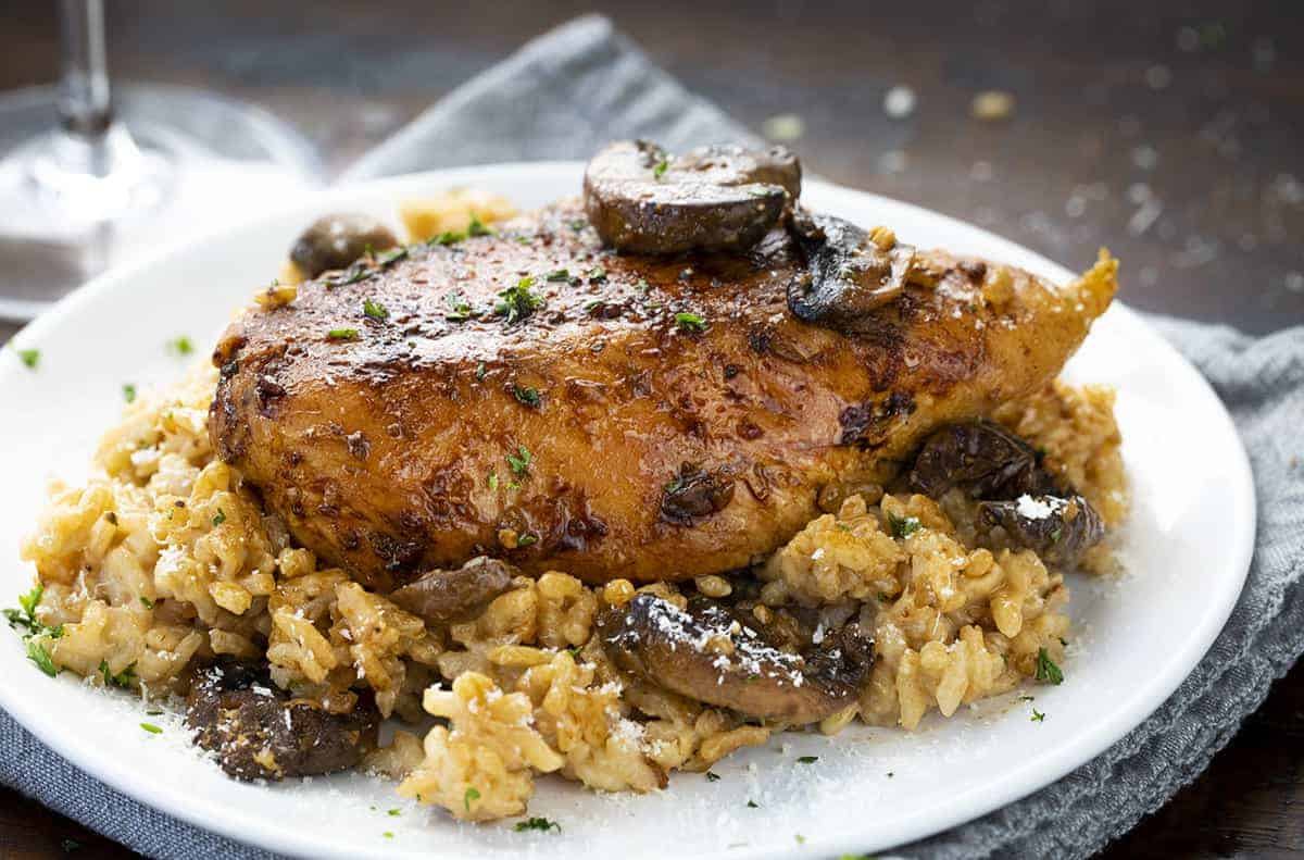 Piece of Chicken Mushroom Risotto on White Plate on Blue Napkin