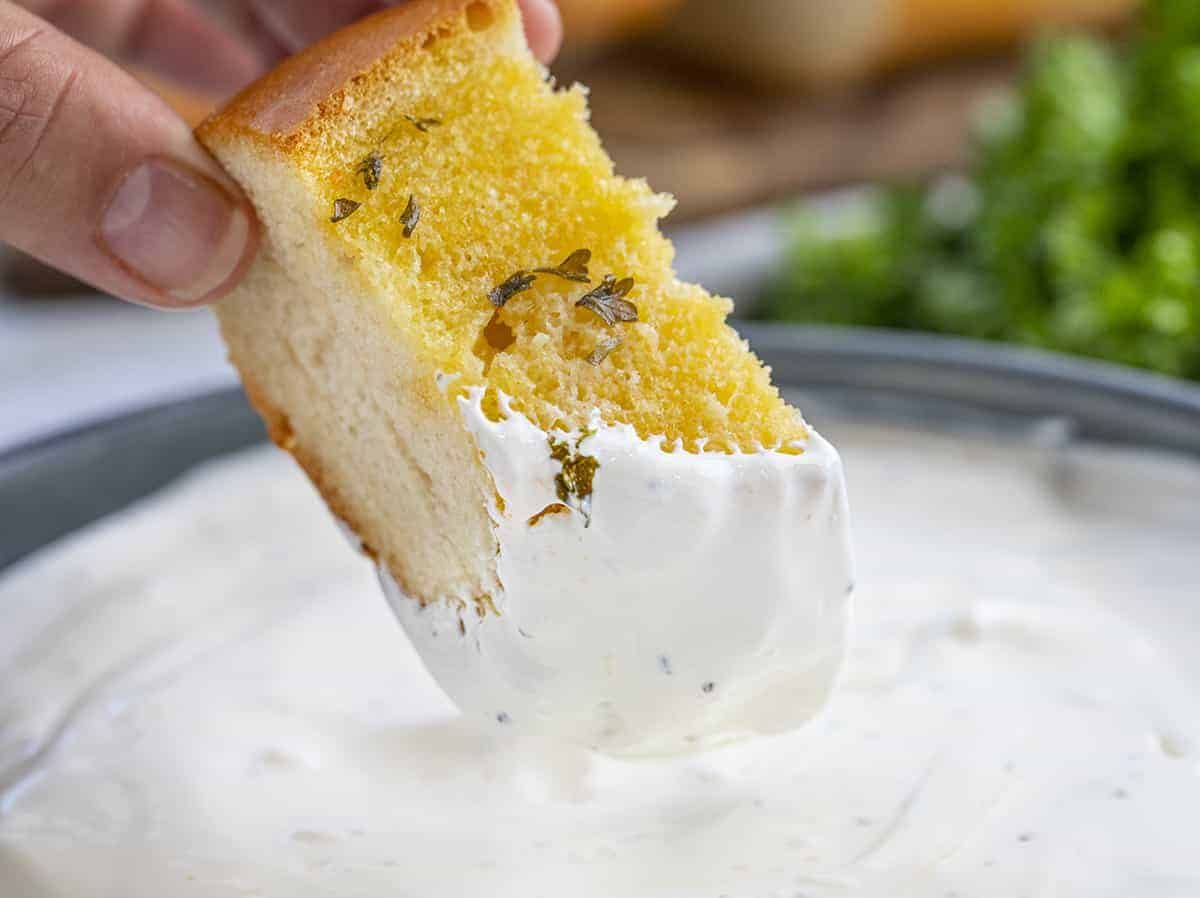Garlic Bread Being Dipped Into a Bowl of Garlic Sauce