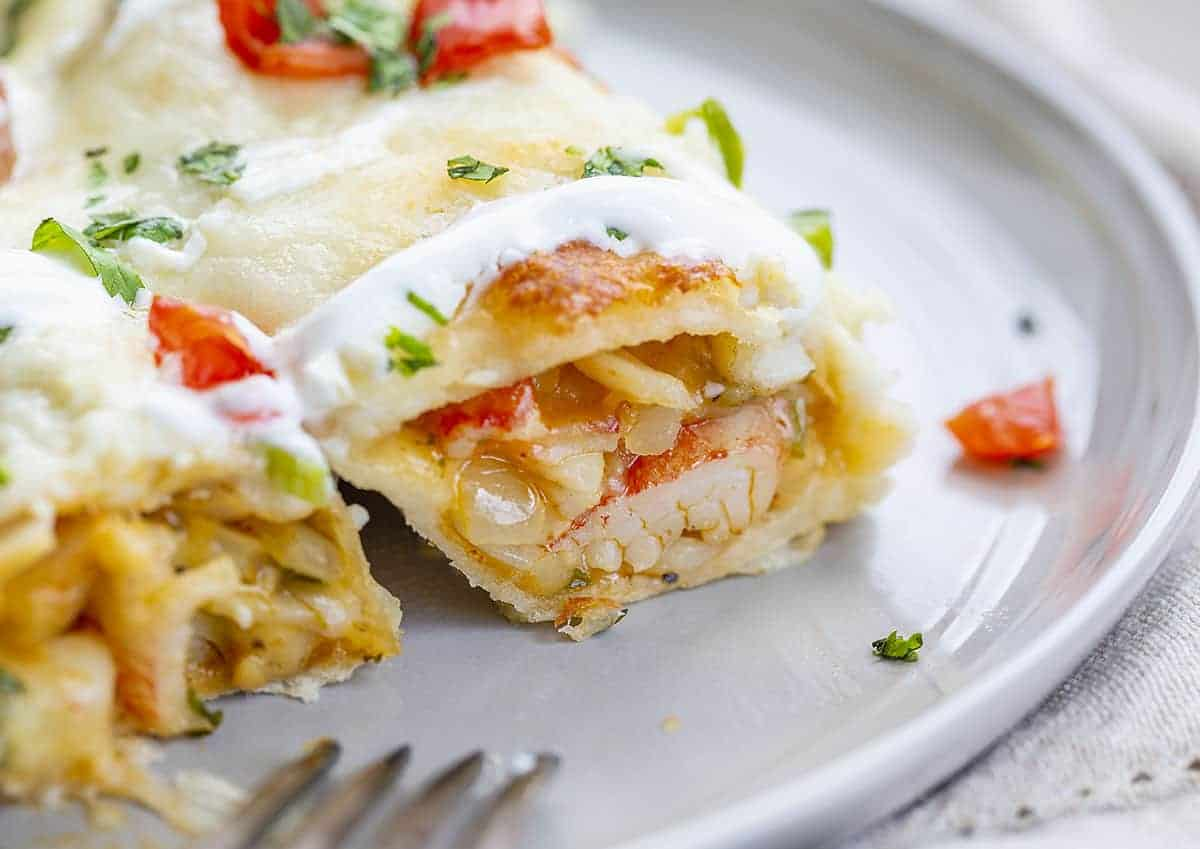 Cut Into Cheesy Seafood Enchiladas on White Plate and Showing Seafood Filling Inside
