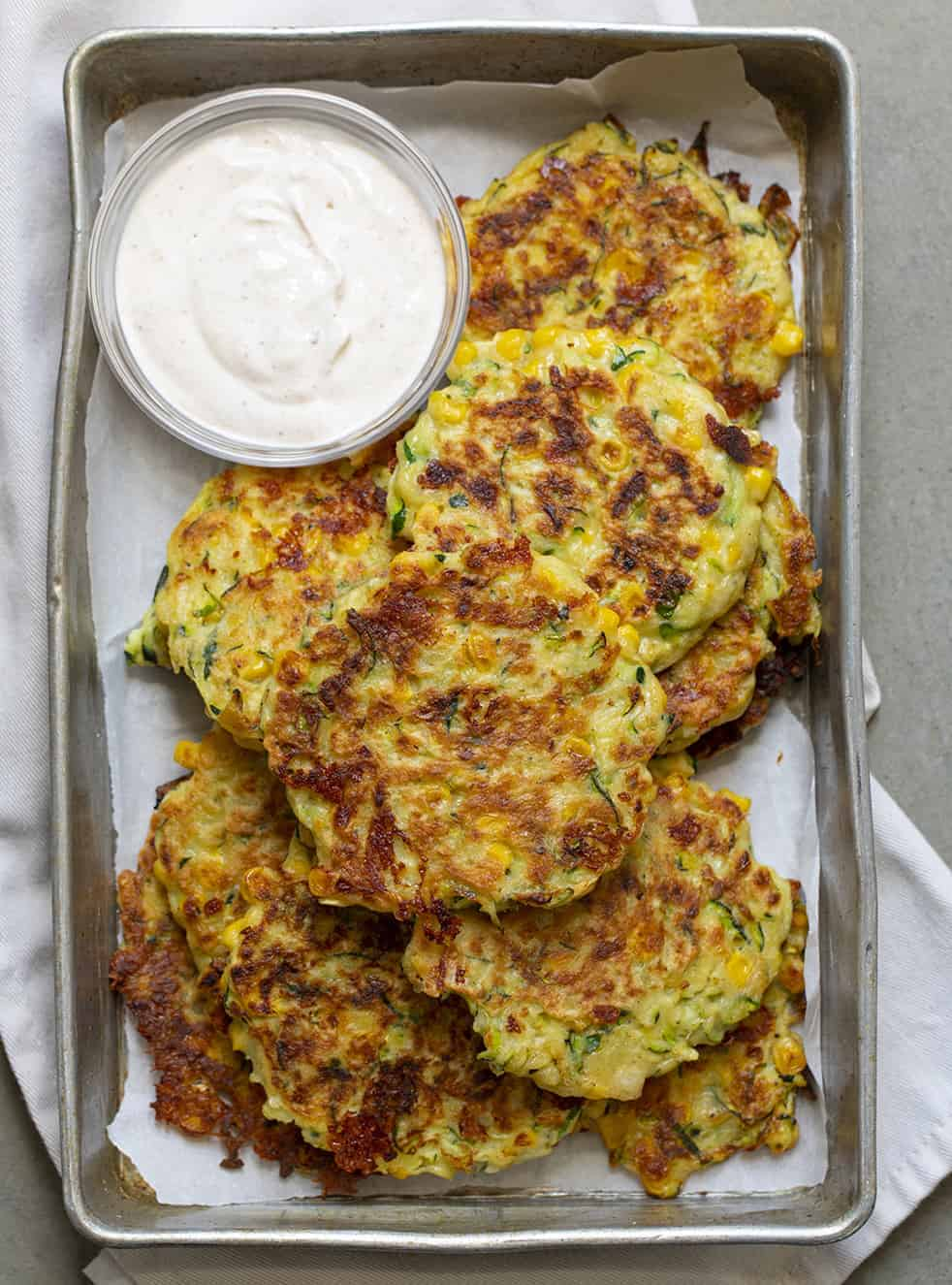 Overhead Image of Zucchini Fritters in a Pan with Sauce