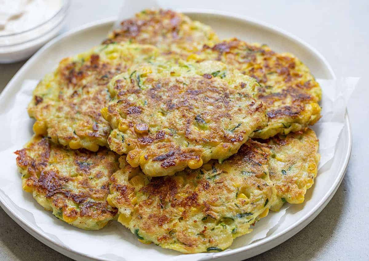 Piled up Zucchini Fritters on a White Plate with Suace