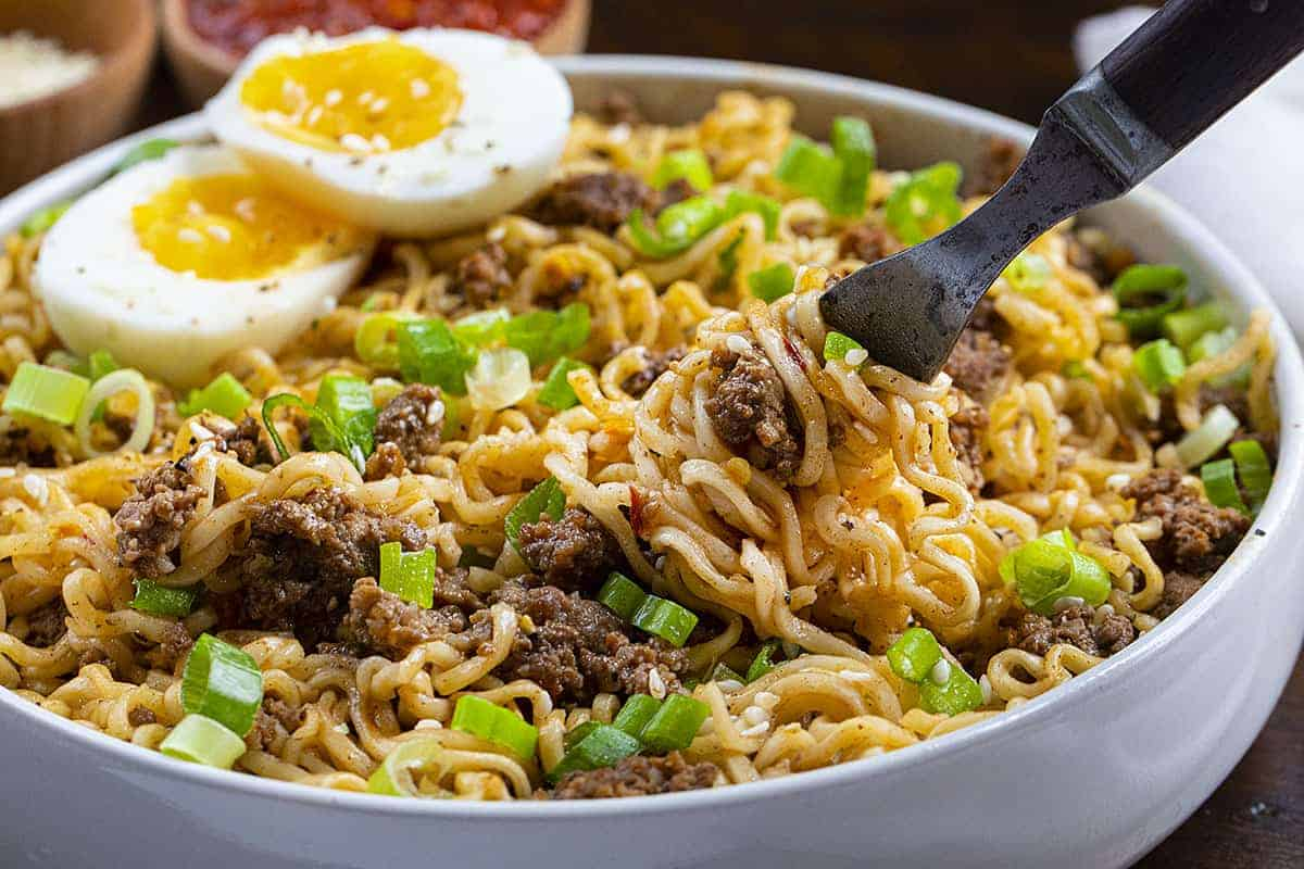 Fork Twirling Spicy Beef Ramen Noodles in a White Bowl