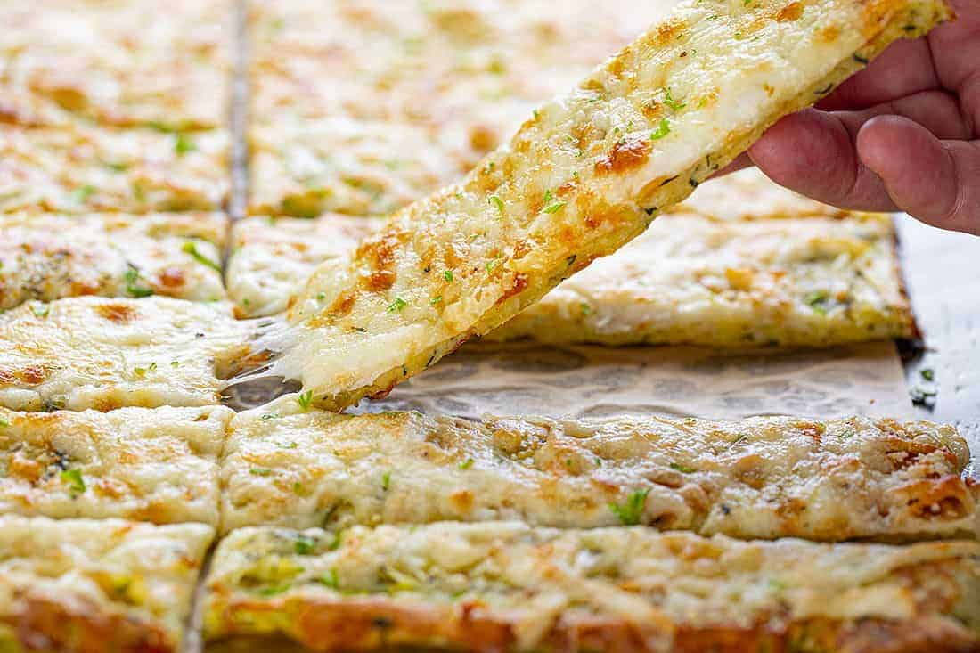 Hand Picking Up a Cheesy Zucchini Breadstick