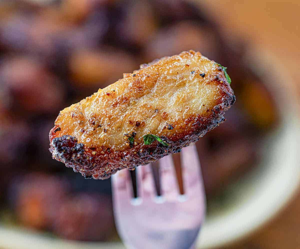 One Crispy Pork Belly Bite on a Fork