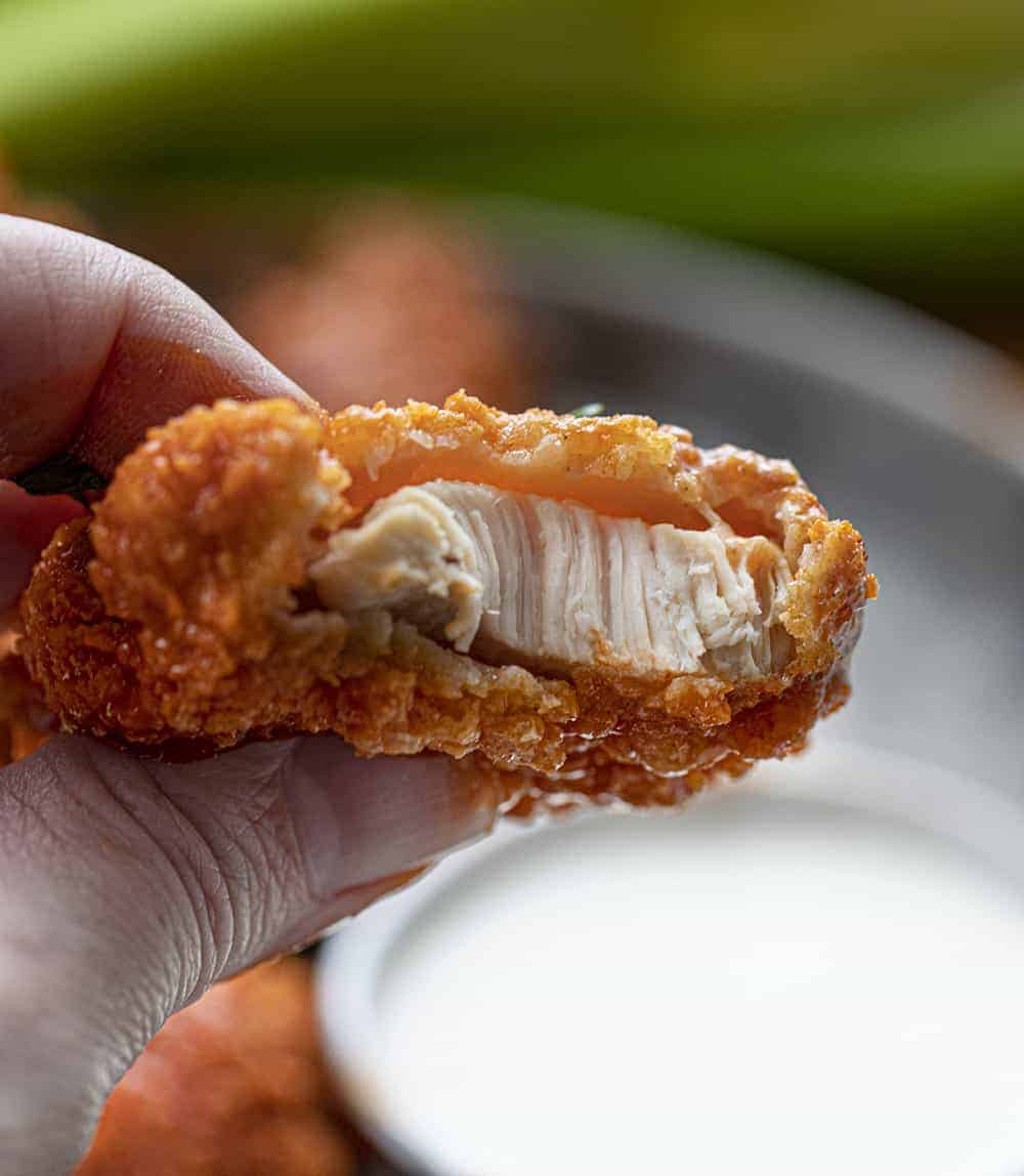 Hand Holding Bit Into Crispy Buffalo Chicken Tender