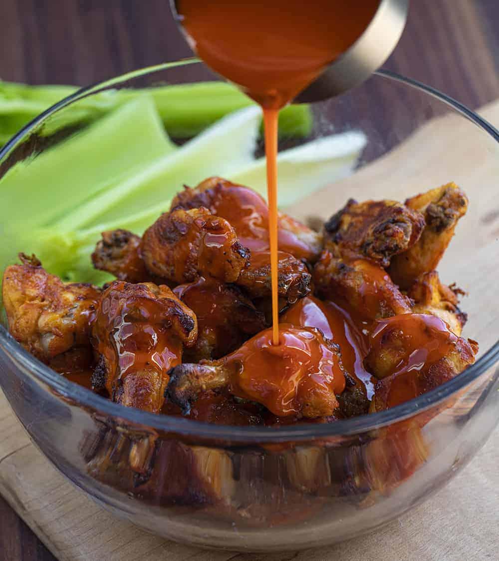 Pouring Buffalo Sauce over Buffalo Chicken Wings