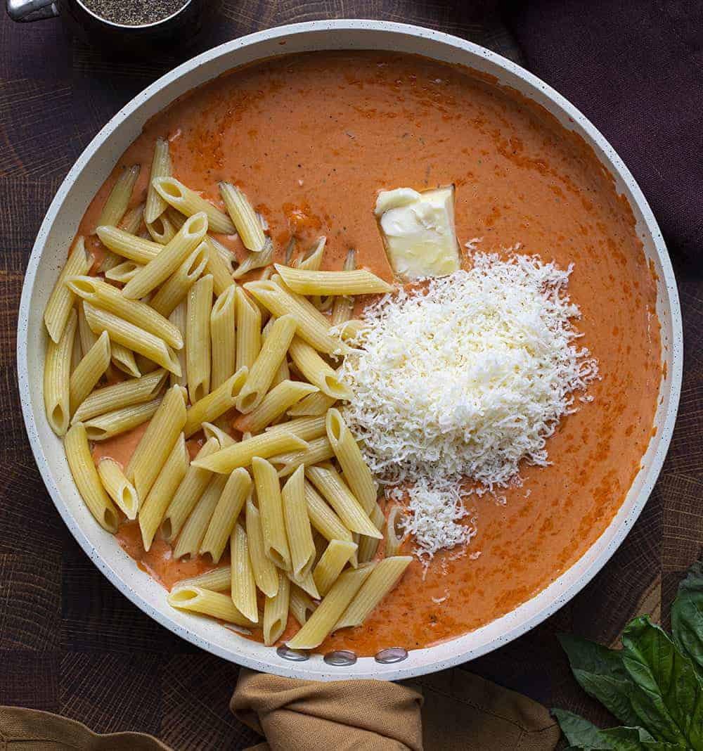 Vodka Sauce in Pan with Parmesan and Noodles Being Added