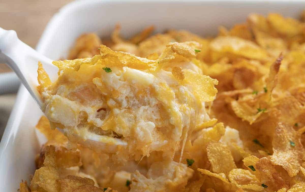 Funeral Potatoes - Cheesy Potato Casserole Being Scooped Out of Pan
