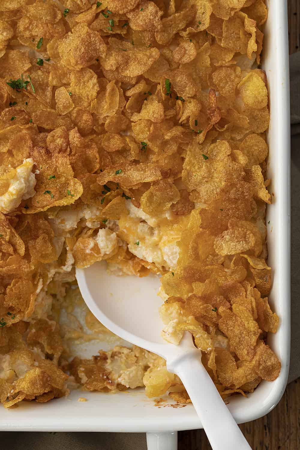Spoon in Pan of Funeral Potatoes - Cheesy Potato Casserole