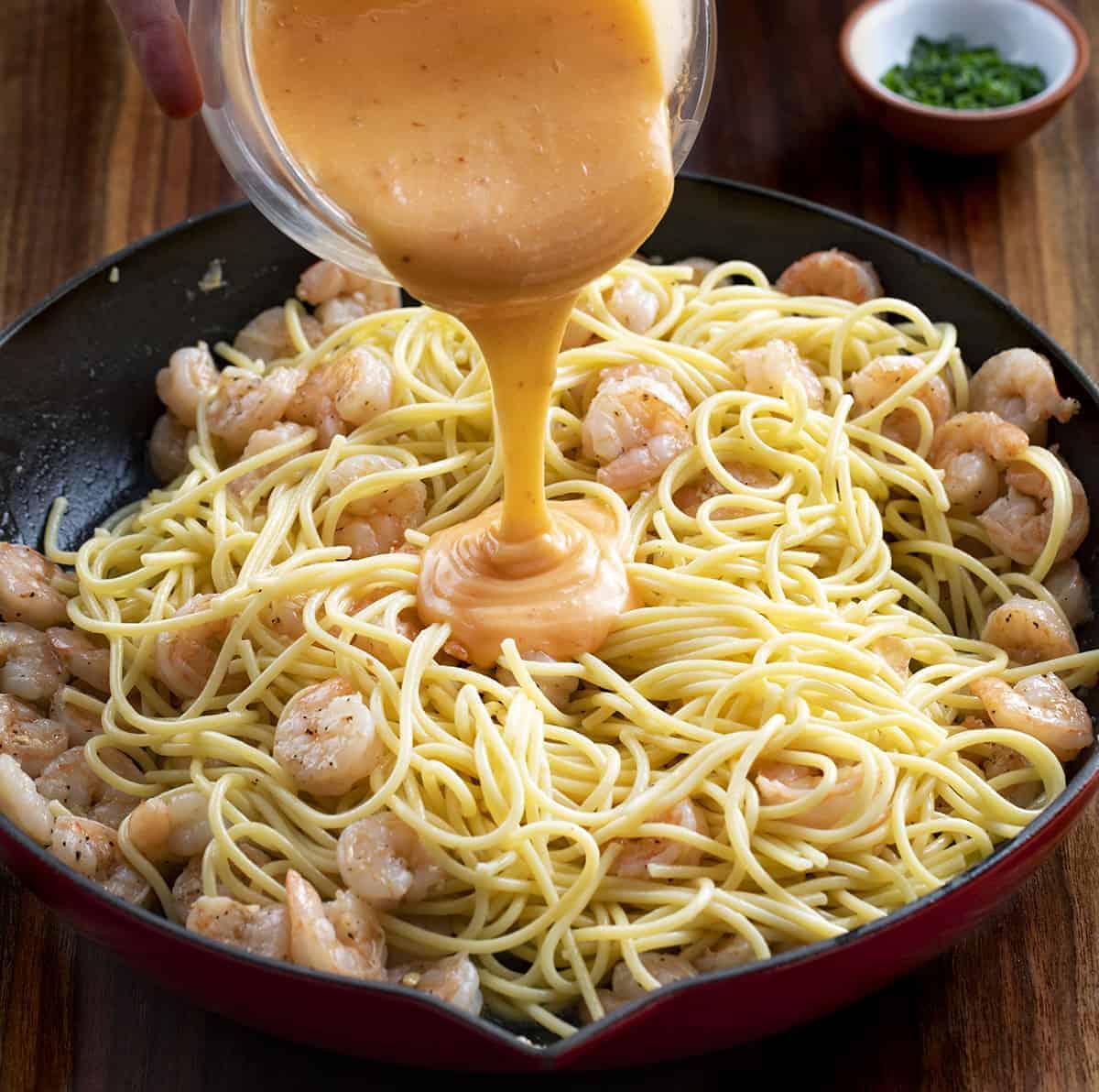 Pouring Sauce on Bang Bang Shrimp Pasta Recipe