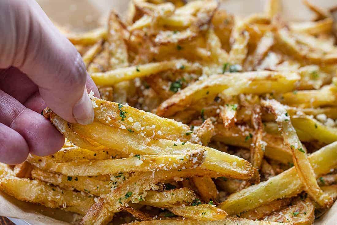 Hand Picking up Garlic Parmesan French Fries