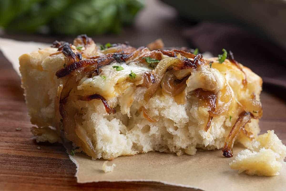Bitten into Piece of Cheesy Onion Focaccia Bread