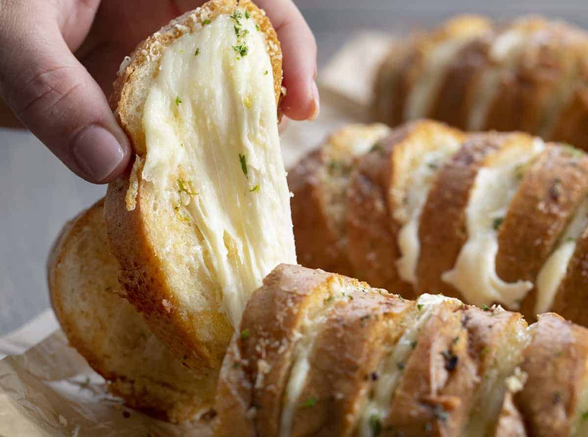 Hand Picking up Hasselback Cheesy Bread
