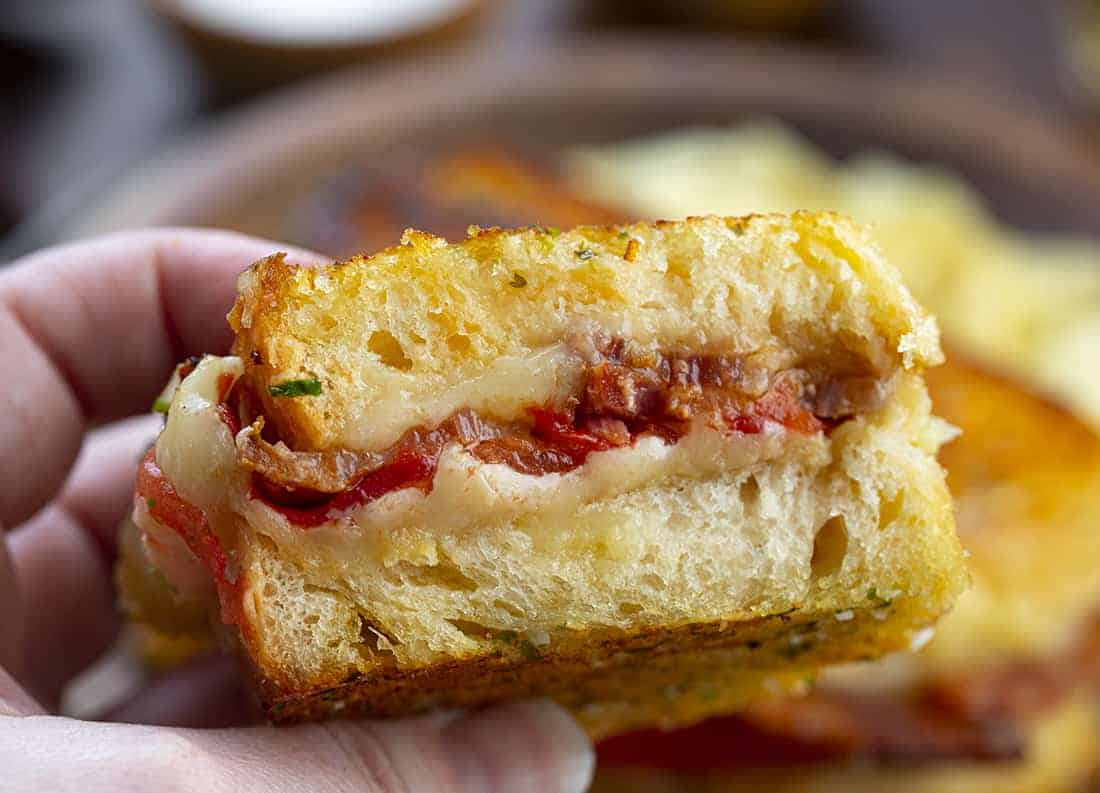 Hand Holding Roasted Garlic Grilled Cheese Sandwich