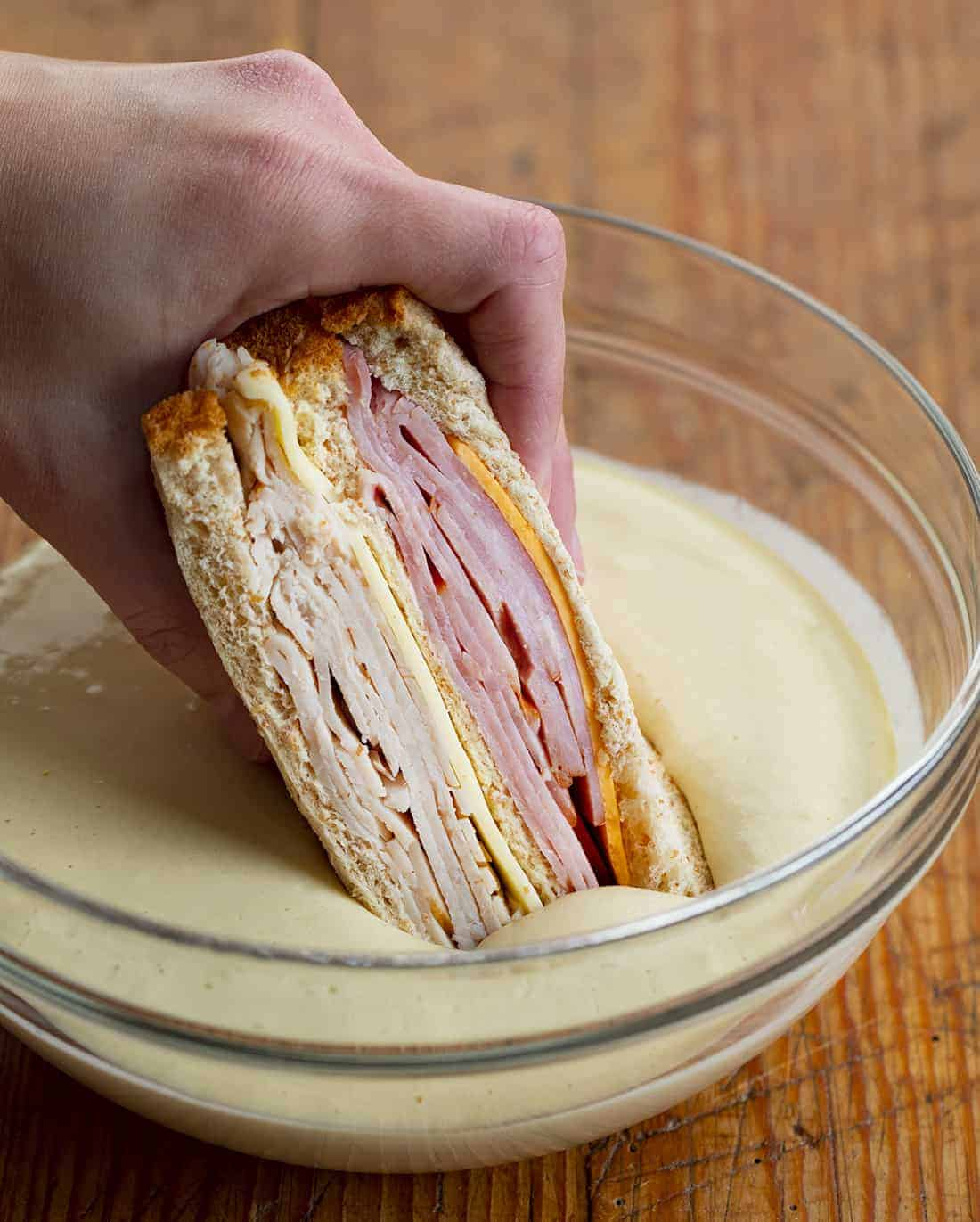 Hand Dipping Monte Cristo Sandwich into Batter